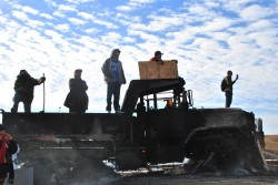 Activists on top of burned out dapl machinery, fires still burning in gas tank - photo by c.s. hagen