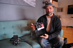 Photographer Kevin Taylor in his studio displaying an old polaroid camera - photo by C.S. Hagen