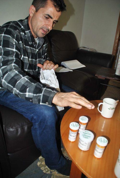 Ezzat Alhaidar showing his PTSD medicines - photo by C.S. Hagen
