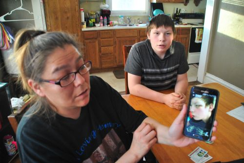 Jackie Charbonneau and her son, Christopher L. Thumb, who is also pictured with two black eyes, and a split lip on cell phone - photograph by C.S. Hagen