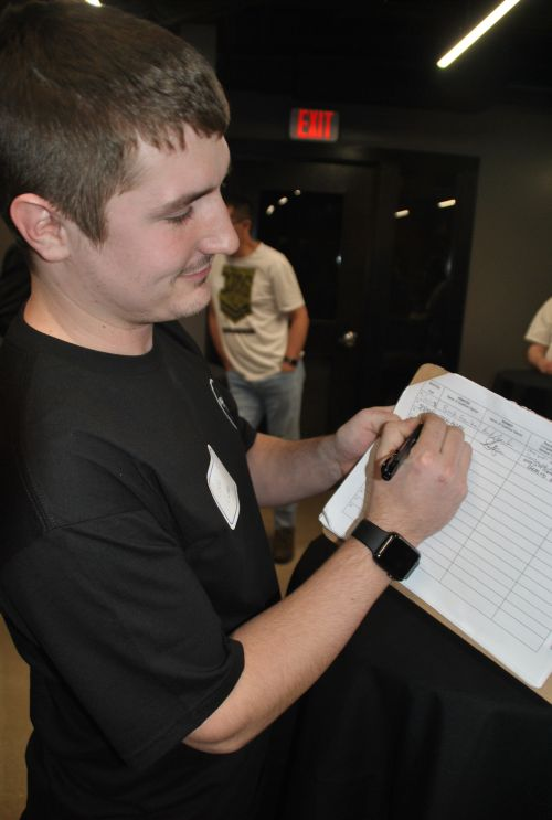 Justin Ludtke, from Mandan, preparing to sign petition - photograph by C.S. Hagen