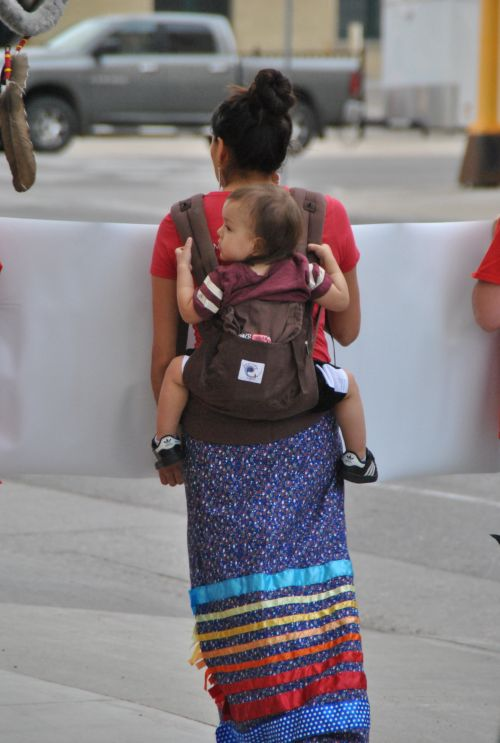 A woman carries child on back while marching for MMIW issues - photograph by C.S. Hagen