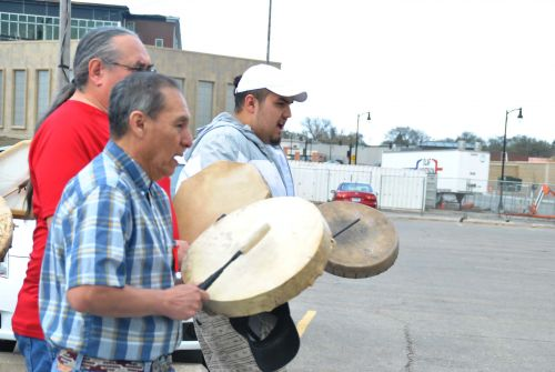 Zebadiah Gartner (in white hat) beats drums and sings during march - photograph by C.S. Hagen