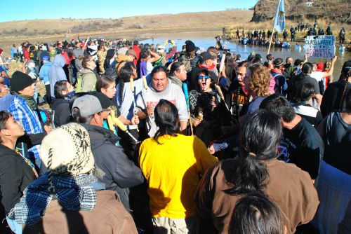 Drums beat while activists face police in ice cold water during the Dakota Access Pipeline controversy - phtograph by C.S. Hagen
