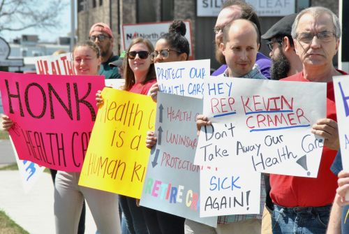 Summer protest outside of Congressman Kevin Cramer's office in Fargo - photograph by C.S. Hagen