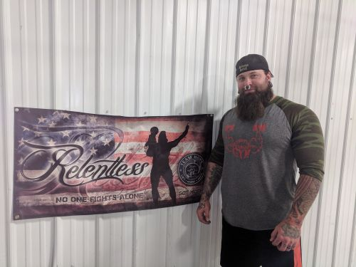 Marshall johnson standing next to a Relentless poster with his and Carter's image