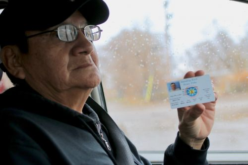 Dale Brave Crow holds up his Standing Rock Sioux Tribe ID card - photograph by C.S. Hagen