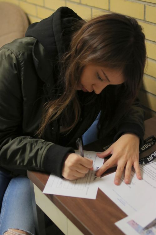 Shaye Eagle Shield, a member of the Standing Rock Sioux Tribe, fills out a Tribal I.D. Form - photograph by C.S. Hagen