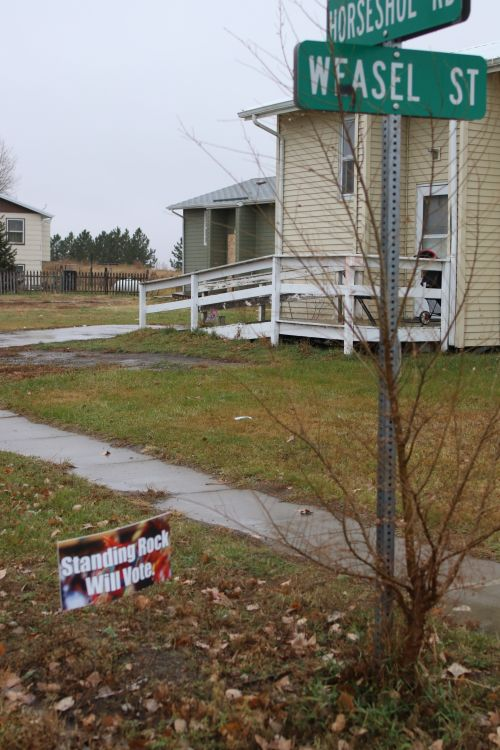 Standing Rock will vote sign beneath Weasel Street and Horseshoe Road in Cannon Ball - photograph by C.S. Hagen