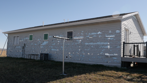 Hail damaged siding with windows already replaced in Pine Ridge, SD - video screenshot by Charles Banner