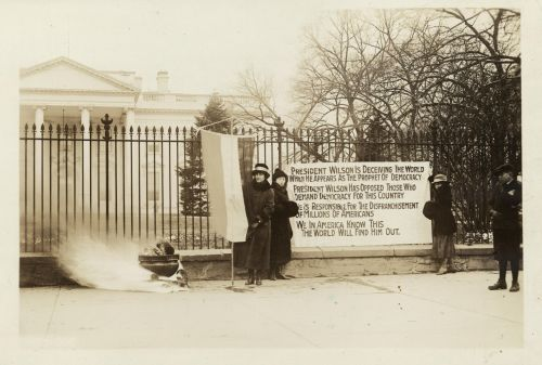 National Woman's Party watchfire demonstrators standing with banners and fire in urn in front of White House during the early 1900s - Harris & Ewing, Washington, D.C