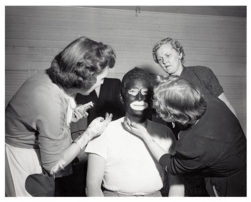 Original cover photograph of a white male in makeup for blackface by three white women at the Fargo Elks Lodge