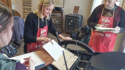 Students learning to operate letterpress equipment - photograph by Suzzanne Kelley