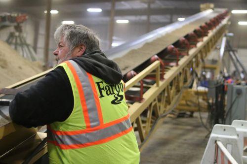 City of Fargo employee watching conveyor belt for clumps - photograph by C.S. Hagen