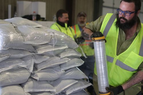 Dylan Sherwood, with the City of Fargo, wrapping up sandbags for transport - photograph by C.S. Hagen