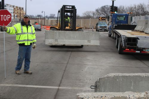 City of Fargo employees work to buffer steel wall over First Avenue North as the Red River creeps closer - photograph by C.S. Hagen