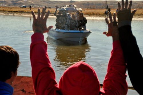 Activists at Standing Rock with raised hands before police and others along far shore - photograph by C.S. Hagen