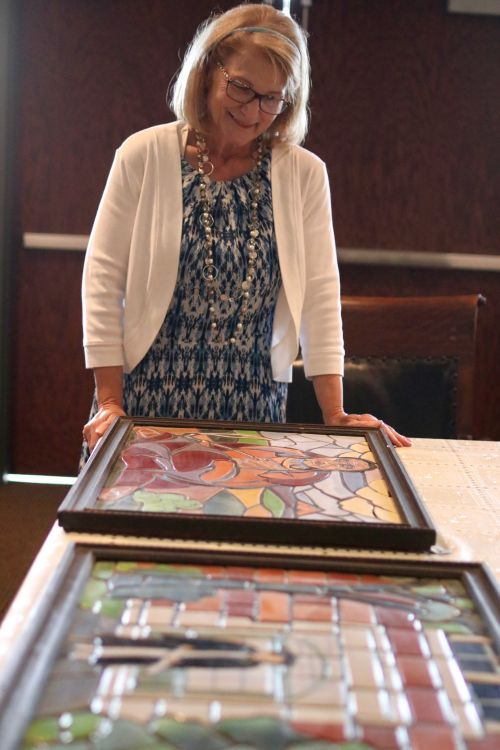 Bonanzaville Executive Director Brenda Warren looks over the Great Depression era mosaics made from North Dakota clay that will be on display and priced during the Antique Road Show - photograph by C.S. Hagen
