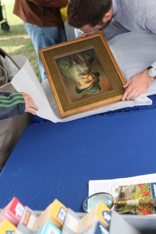 Antique Roadshow appraiser inspecting a painting - photograph by C.S. Hagen