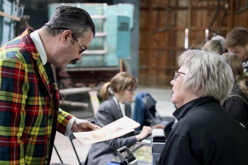 Appraiser Nicholas Lowry investigating a print - photograph by C.S. Hagen