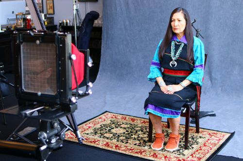 New Mexico Representative Debra Haaland sitting for a wet plate photograph with Shane Balkowitsch in viewfinder - photograph by C.S. Hagen