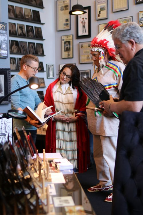 South Dakota Representative Tamara St. John - center - looking at a book by photographer Edward Curtis with Shane Balkowitsch - photograph by C.S. Hagen