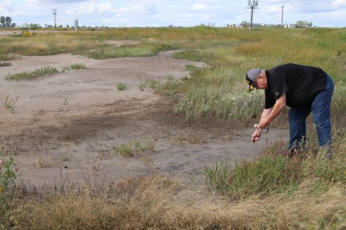 Daryl Peterson a retired Bottineau County farmer checking for salt levels at a spill site - photograph by C.S. Hagen