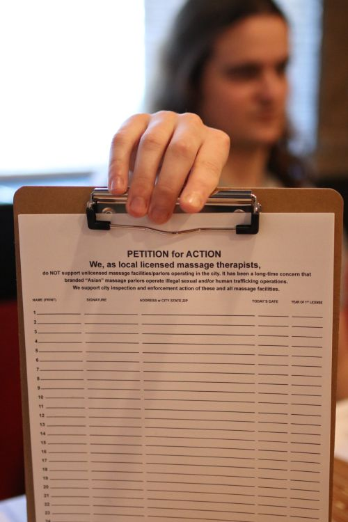 Keith Coates holds up petition that will work its way to the state legislature to stop human trafficking - photograph by C.S. Hagen