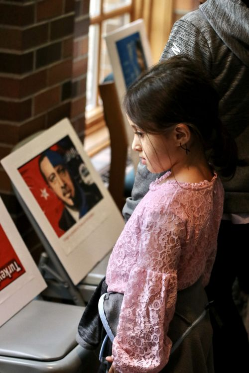 A young girl looks on a protest posters containing pictures of the Turkish president - photograph by C.S. Hagen