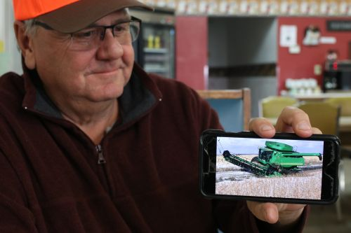 Bob Bowerman, a Kidder County farmer, holds up a picture of his combine stuck in the mud - photograph by C.S. Hagen