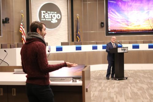 Fargo City Commissioner John Strand listens while residents speak their views on climate change - photograph by C.S. Hagen