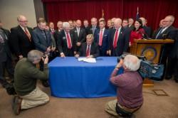 Gov. Jack Dalrymple signing a $1.1 billion surge funding bill