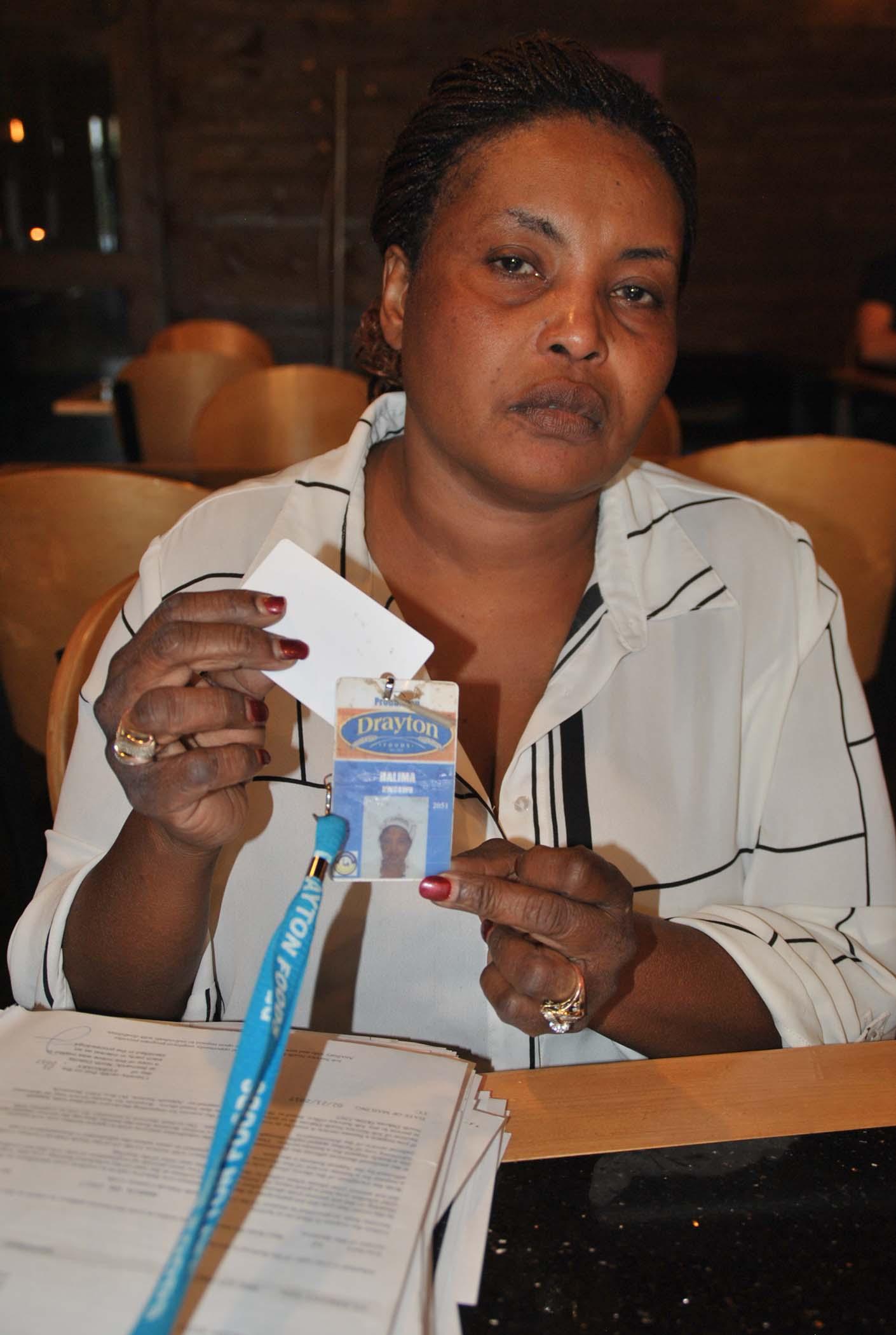 Halima Kwcrwb holds up her Drayton work tag - photo by C.S. Hagen