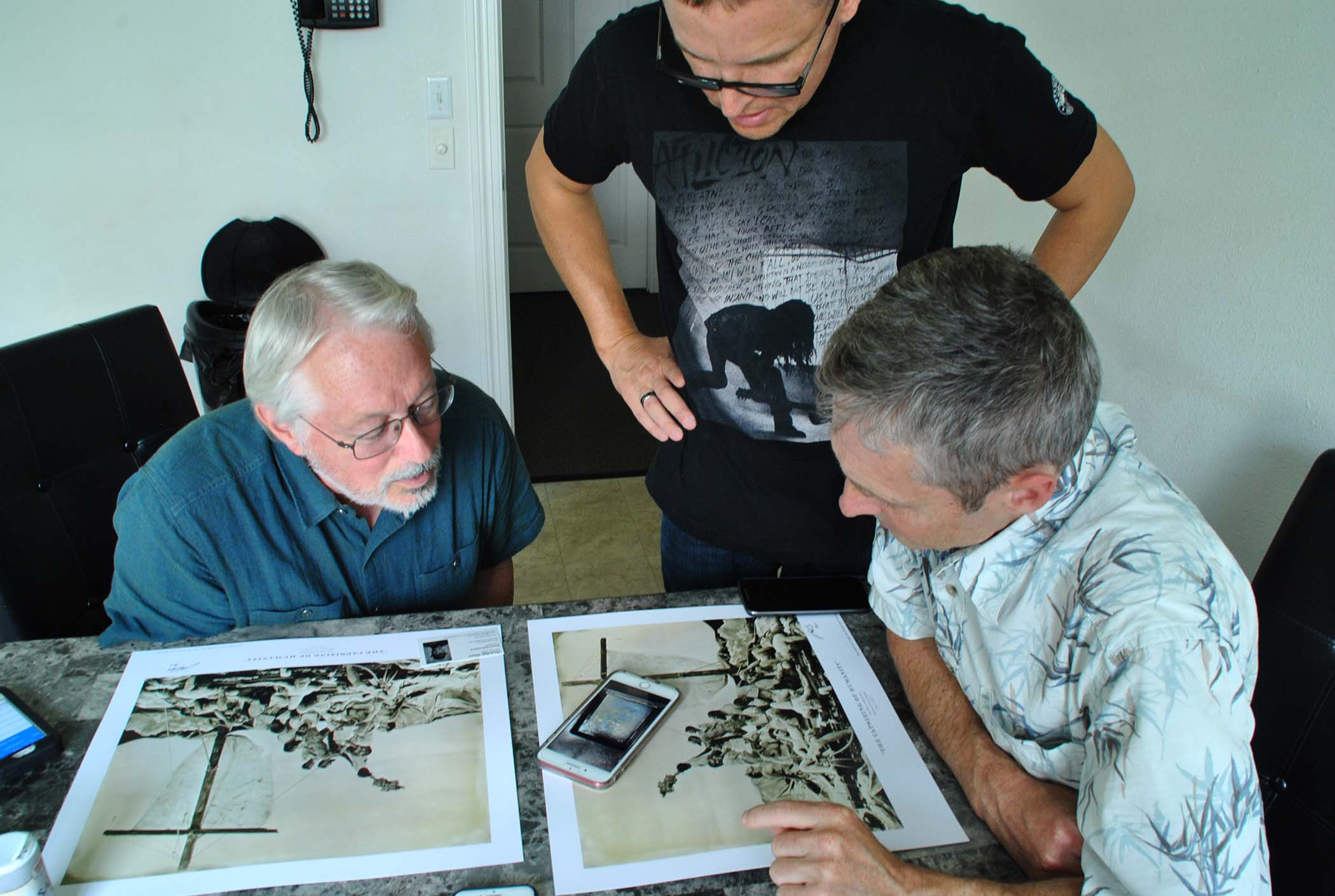 Michael Foster and Leonard Higgins, both valve turners, discuss a wet plat photograph event with Bismarck native Shane Balkowitsch - photo by C.S. Hagen