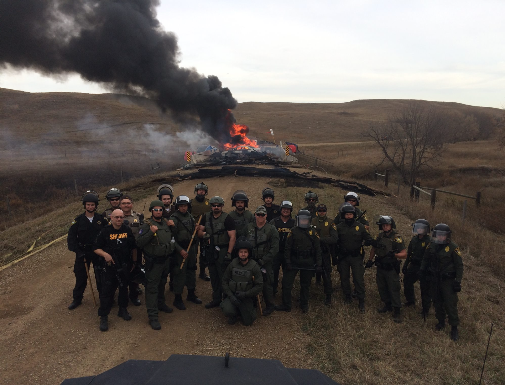 Police gather for a photo opp before a roadblock setup by activists, reports differ on who set the debris on fire - photo provided by online sources