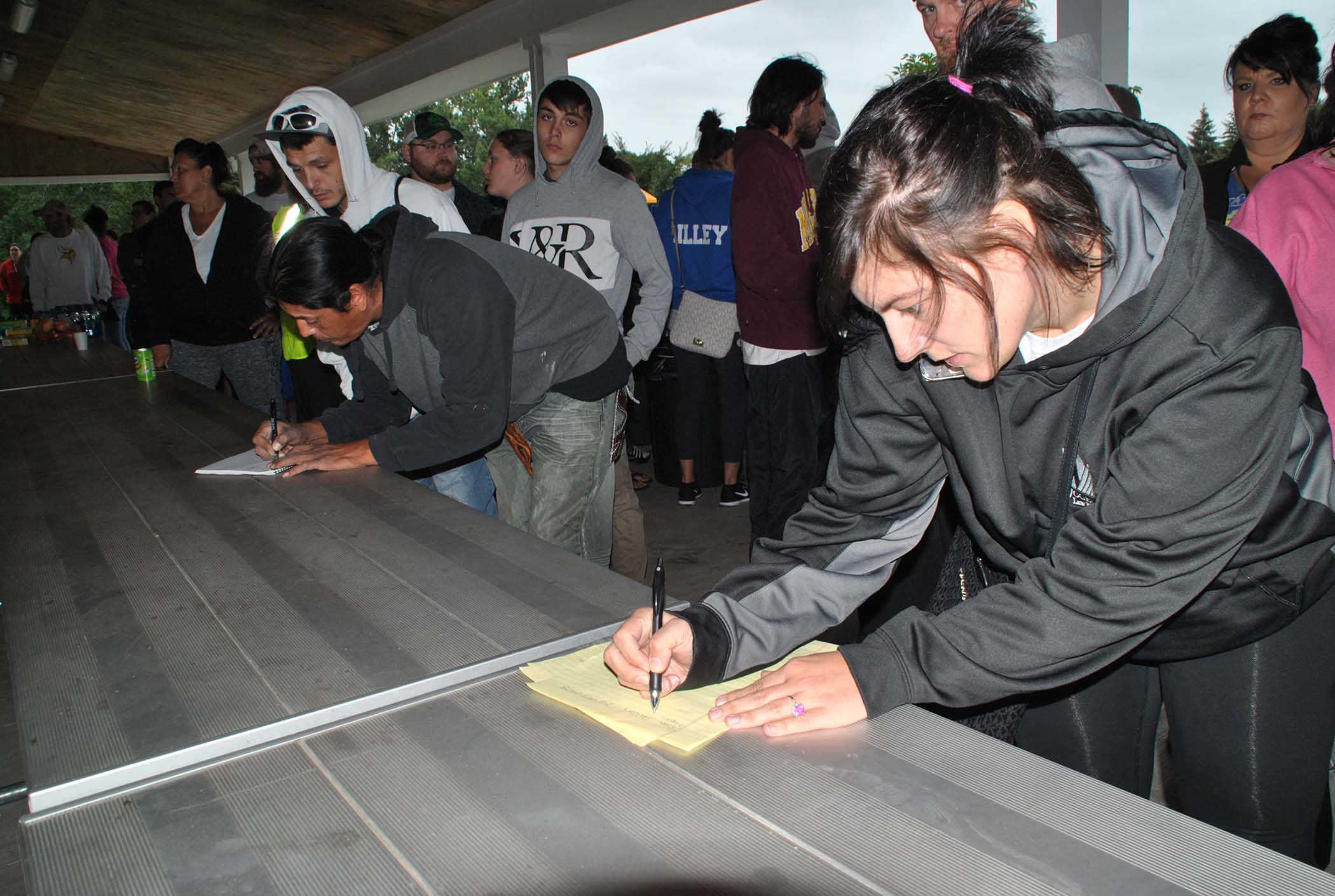 Search volunteers line up to write down names - photo by C.S. Hagen