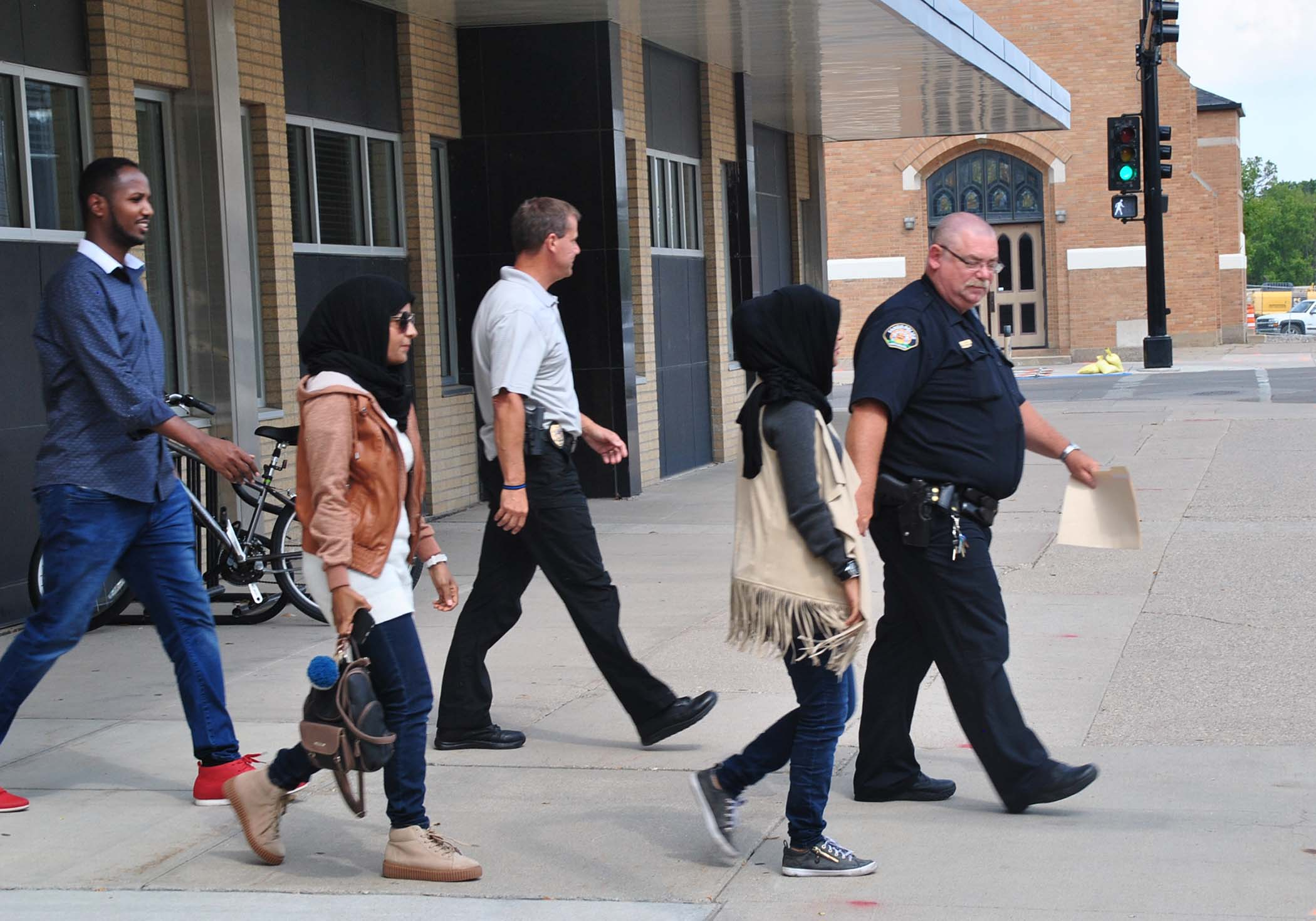 The Hassan sisters accompany police officers to a scheduled meeting with their attacker - photo by C.S. Hagen