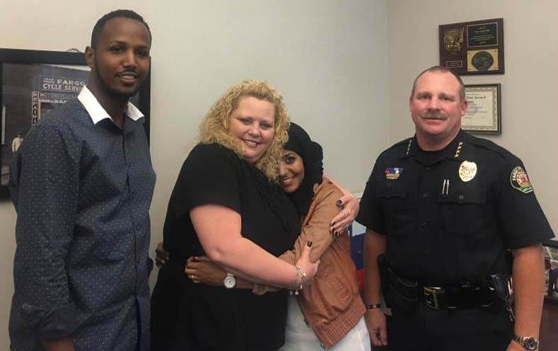 Victim of hate crime, Sarah Hassan hugs her attacker Amber Elizabeth Hensley Thursday at the Fargo Police Department - photo provided by Hukun Abdullahi