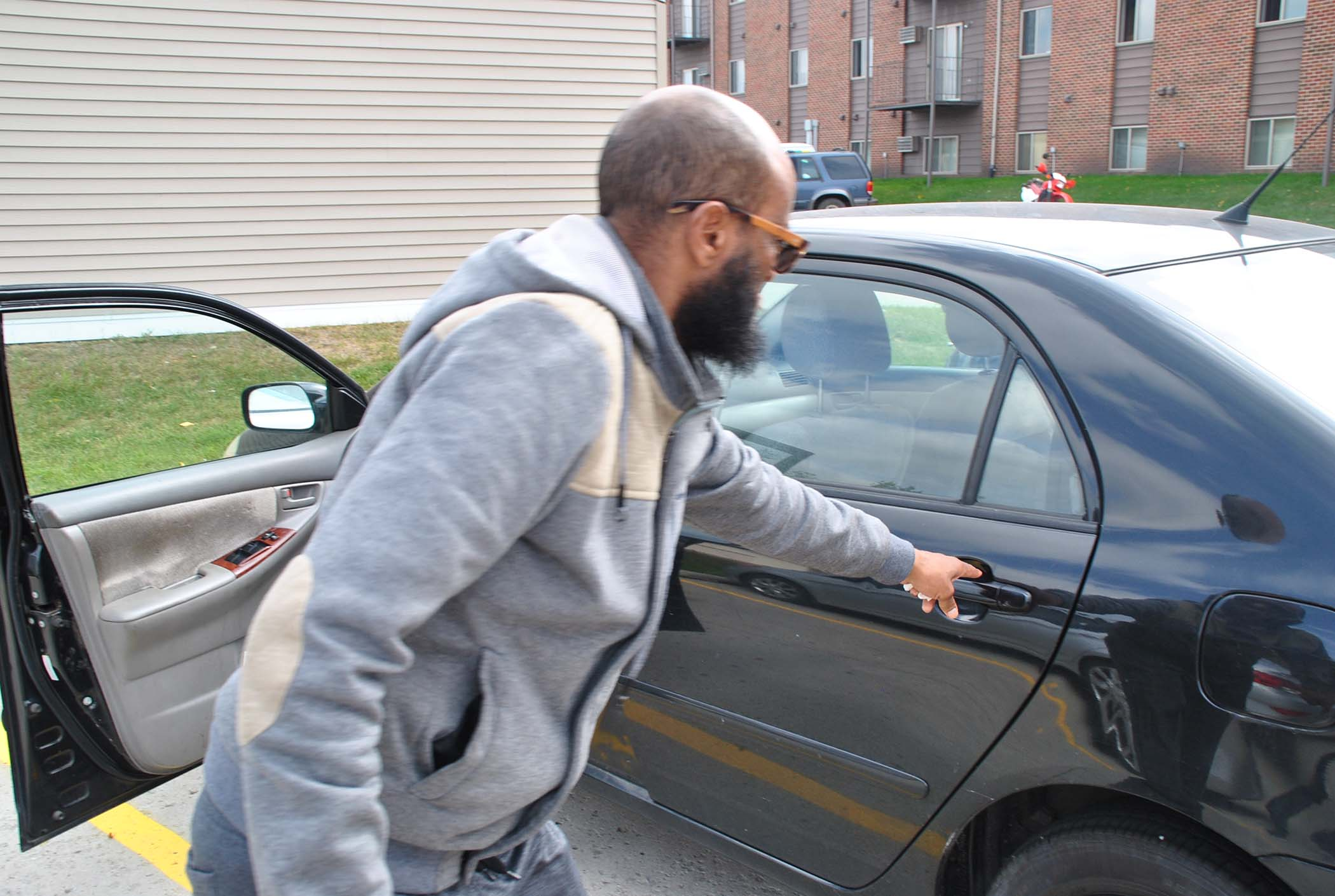 Yusuf Mohamed preparing to open his car's door - photo by C.S. Hagen